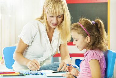 Cute little girl having speech therapy with young female speech/language therapist in a office. Therapist showing illustration to hear how she pronouncing some letters. Selective focus to young woman. They are drawing together also.